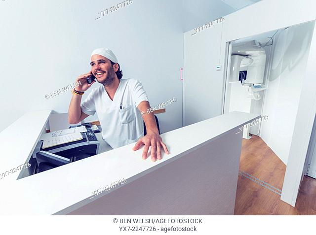 Dentist in reception area speaking on the phone