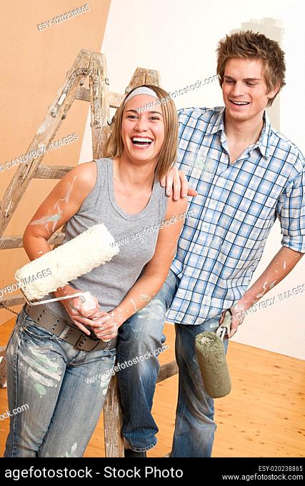 Home improvement: Young couple painting wall