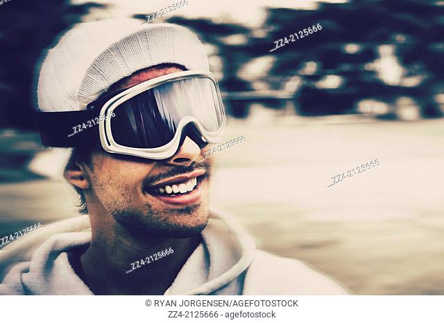Head on portrait of a male snowboarder wearing ski goggles and smile, tobogganing in motion on a downhill ski slope