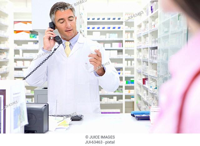 Pharmacist on telephone, reading label on back of medicine pot, behind pharmacy counter