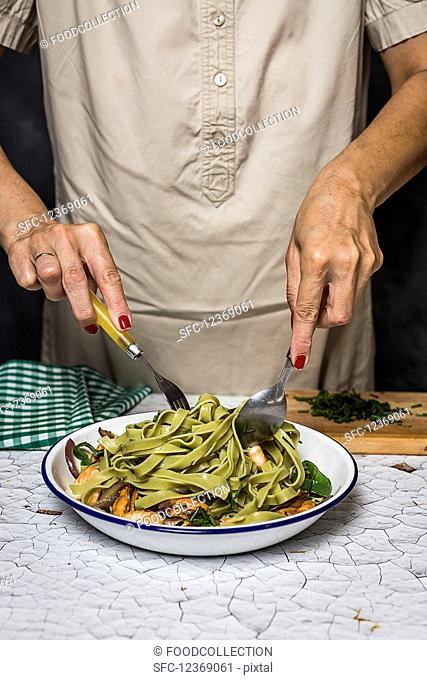 A woman serving green tagliatelle with seafood