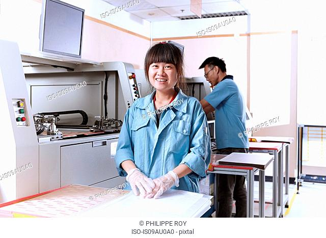 Young woman in flexible electronics plant looking at camera smiling