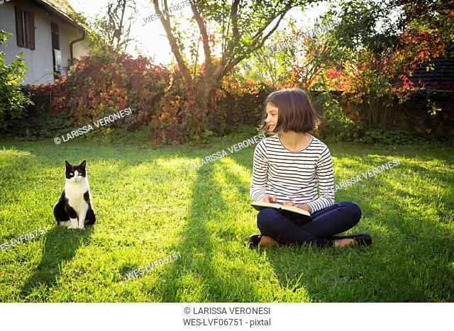 Smiling girl sitting on meadow with a book next to cat