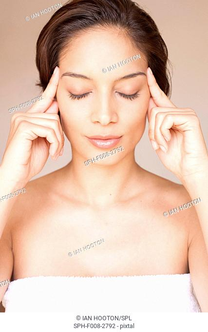 MODEL RELEASED. Woman massaging her face