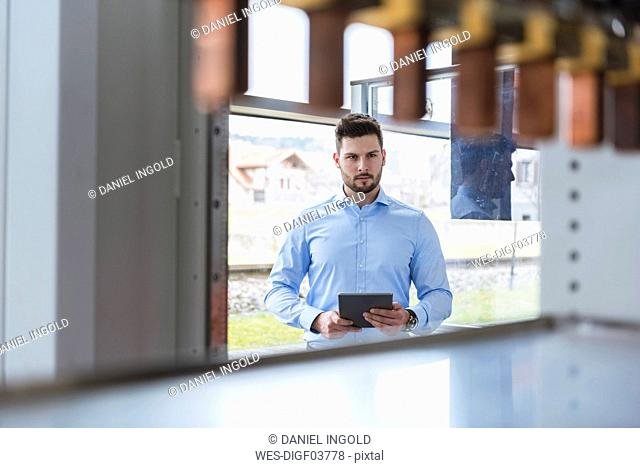 Businessman with tablet in company looking at product