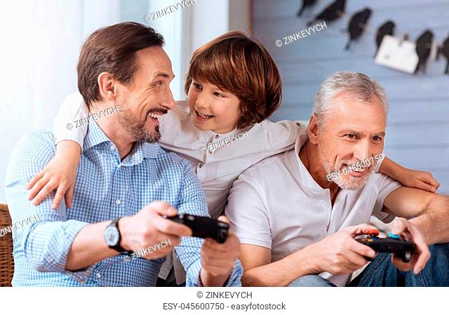 Video games. Nice delighted positive men sitting together and holding game consoles while playing video games