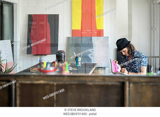 Artist at work, drawing in a notebook in his loft studio