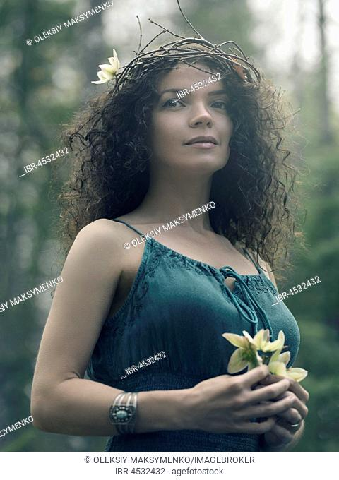 Romantic outdoor portrait of a beautiful young woman with a dreamy serene look on her face, wearing a wreath made of tree branches and a green dress holding a...