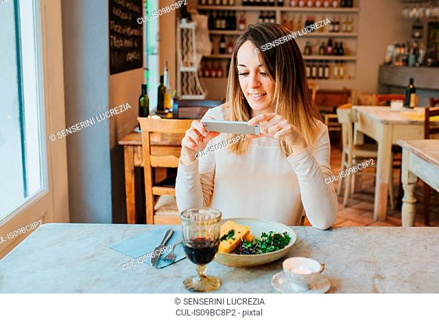 Woman taking photo of vegan meal in restaurant