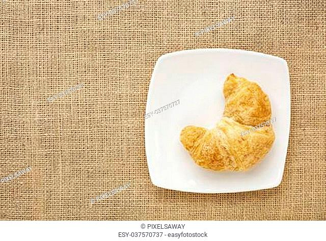 croissant roll on a white china plate against burlap canvas board