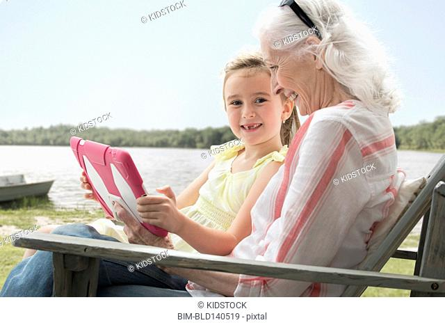 Caucasian grandmother and granddaughter using digital tablet