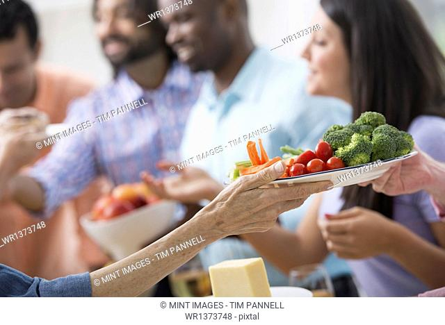 An open plan office in New York City. A working lunch, a salad buffet. A group of men and women of mixed ages and ethnicities meeting together