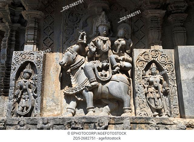 Sculptures on the façade, west side walls. Shiva-Parvati on sitting Nandi. Hoysaleshwara temple, Halebidu, Karnataka, india