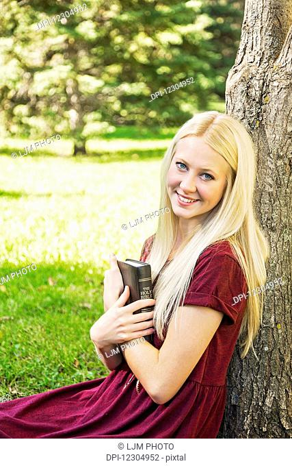 A young woman holding her Bible close to her chest while spending personal devotional time outdoors in a park in autumn; Edmonton, Alberta, Canada