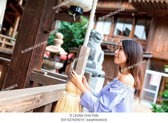 Woman holding the rope of the bell in Japanese temple
