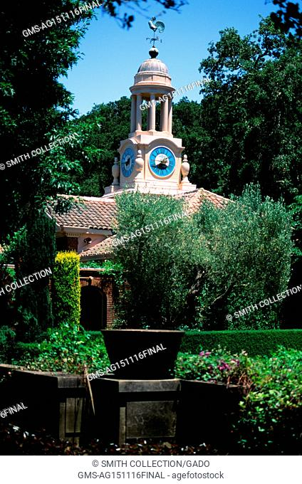 A clocktower in the California Eclectic architectural style is visible among plants and a formal hedgerow at Filoli Gardens