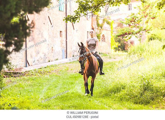 Woman riding horse looking at camera smiling