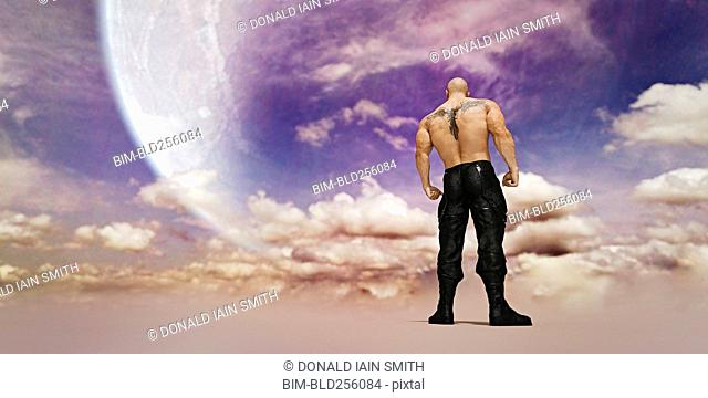 Strong man with tattoo on back standing in clouds