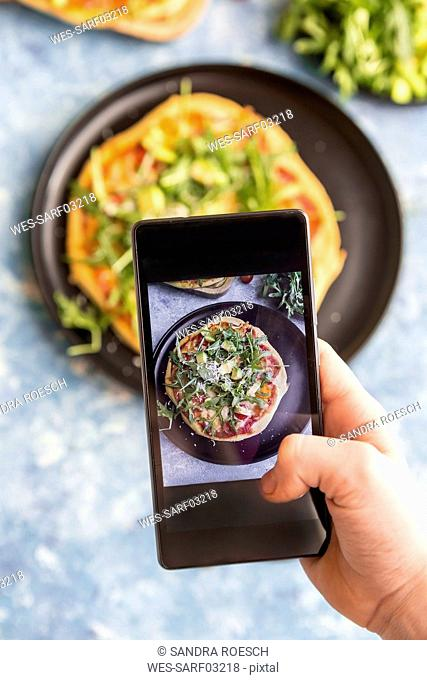 Hand of girl taking picture of homemade vegetarian pizza with cell phone, close-up