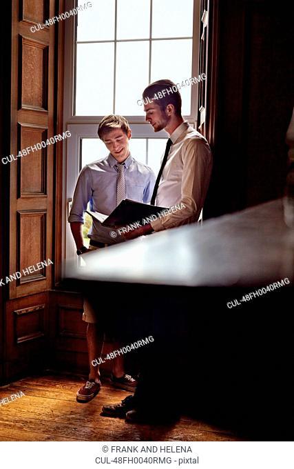 Businessmen talking by window