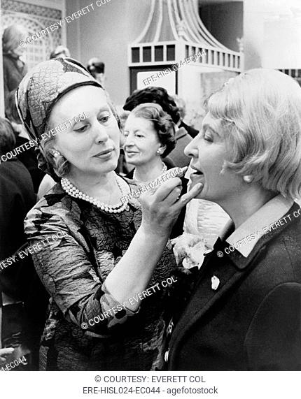 Estee Lauder 1906-2004 cosmetics business leader dressed in an Yves Saint Laurent dress applies lipstick to a customer in New York City. 1966