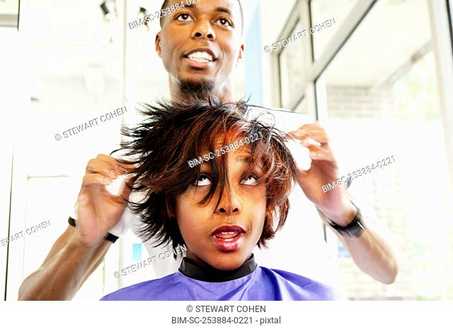 Hairdresser working on young woman's hair