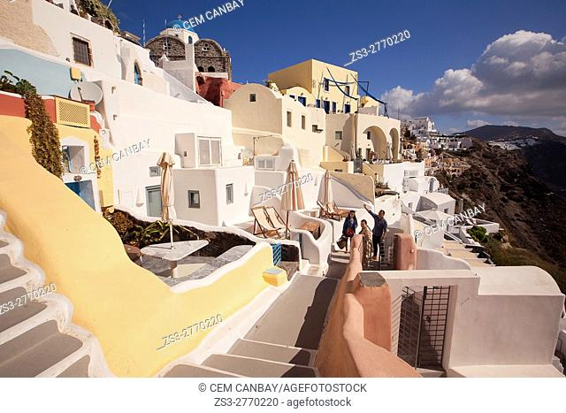 View to the traditional Cyclades houses in Oia village with a blue dome church at the background, Santorini, Cyclades Islands, Greek Islands, Greece, Europe