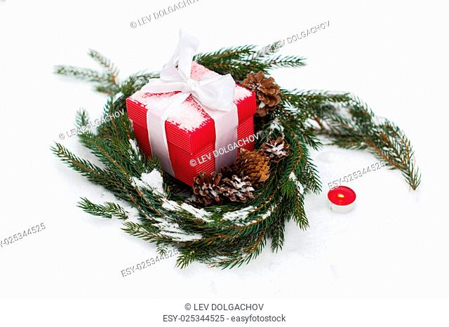 christmas, winter holidays and greeting concept - gift box and fir wreath with cones on snow