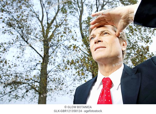 Close-up of a businessman shielding his eyes