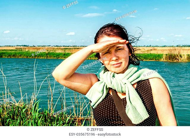 Woman looking into the distance on background river