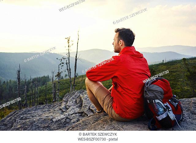 Man sitting on rock enjoying the view during hiking trip