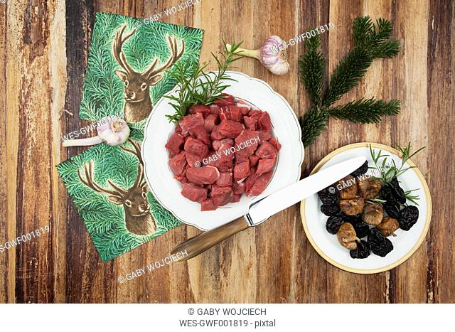 plate of raw cubed venison meet, garlic bulbs, dried figs, plums, rosemary and carving knife on wooden background