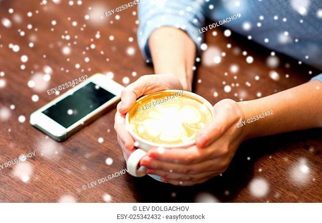 drinks, people, technology and lifestyle concept - close up of young woman with smartphone drinking coffee at cafe over snow