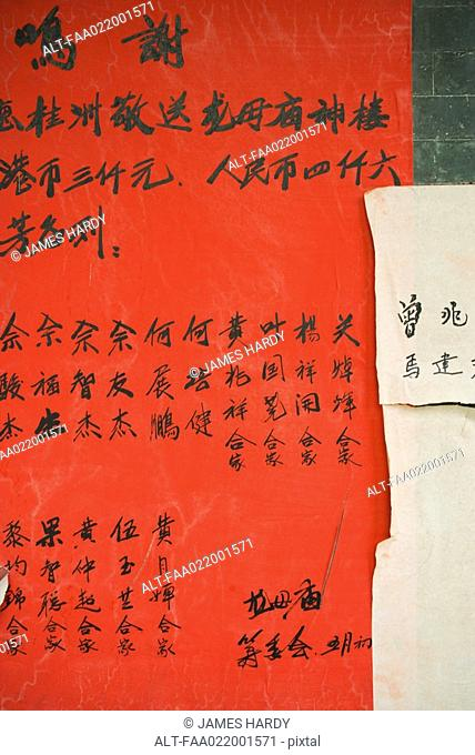 Handwritten chinese characters on ad posted on wall, close-up
