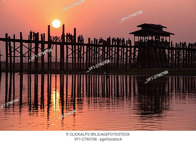 Amarapura, Mandalay region, Myanmar. Silhouetted people walking on the U Bein bridge at sunset