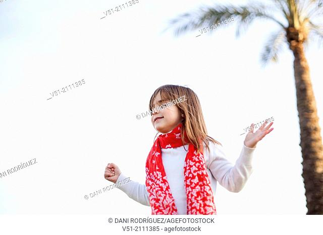 Young girl with eyes closed and arms opened at the sea