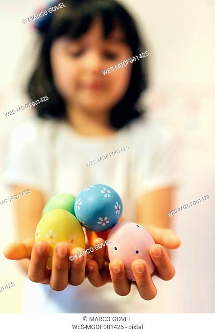 Girl's hands holding painted Easter eggs