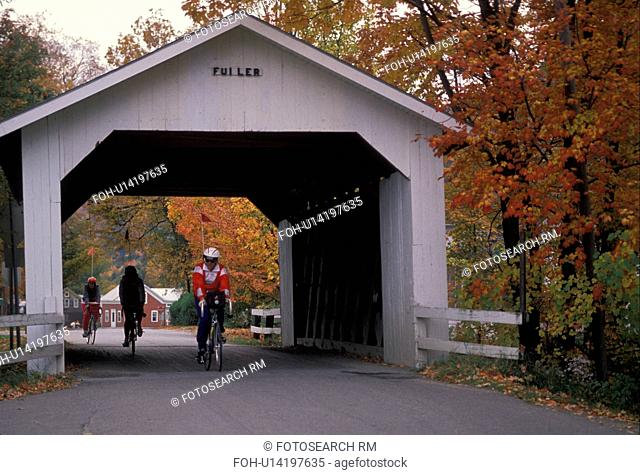 covered bridge, fall, cyclist, bike, Vermont, Montgomery, People riding bikes through Fuller Covered Bridge (circa 1890) surrounded by fall foliage in...