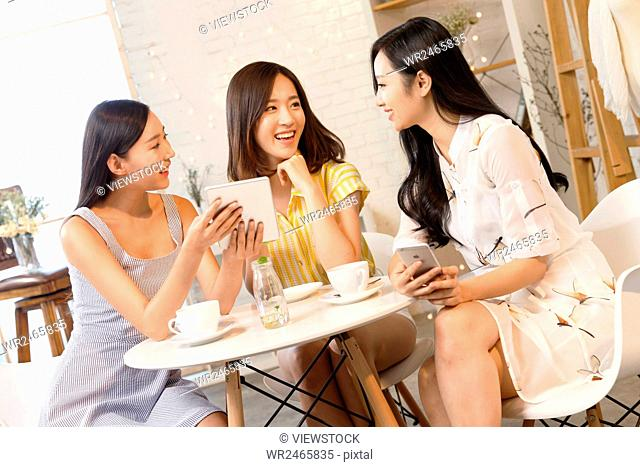 Three young women sitting at a table looking at digital tablet