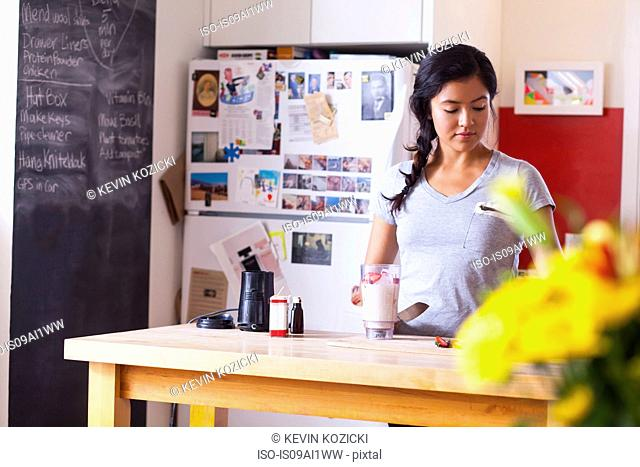 Young woman blending fruits in kitchen