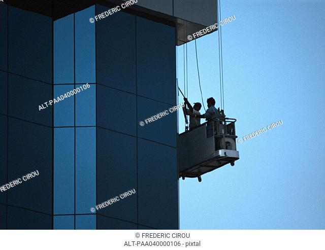 Two men cleaning skyscraper's windows