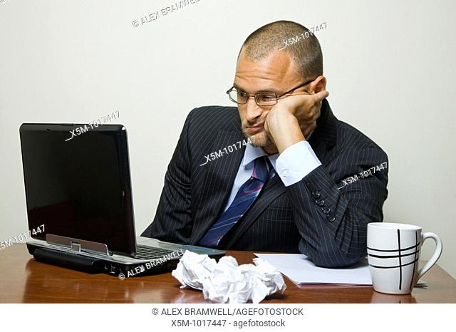 Bored businessman in an office cubicle or home office with a laptop and a fed up look on his face
