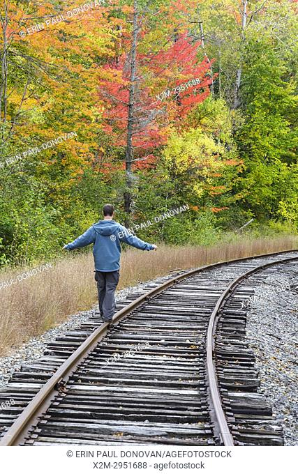Man balancing on the railroad tracks of the old Maine Central Railroad in Carroll, New Hampshire USA