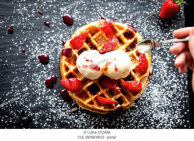 Female hand holding spoon over strawberries and ice cream waffle on slate