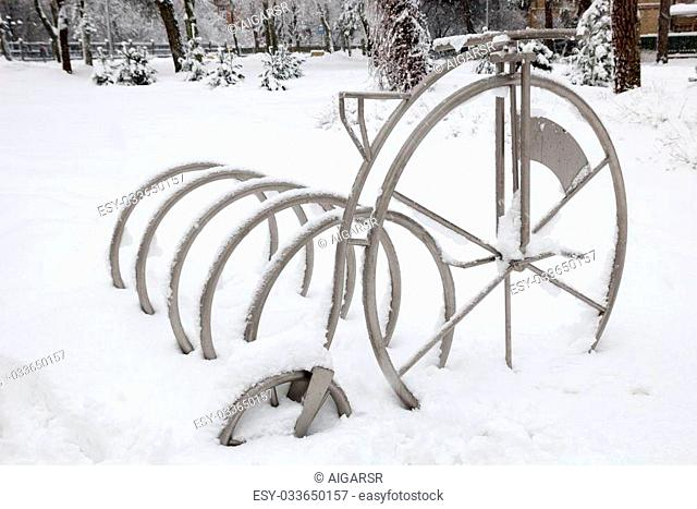 Snow in the city park. Snow covered bicycle stand