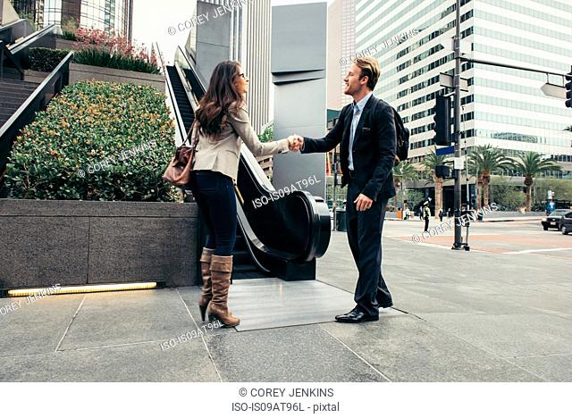 Businessman and woman shaking hands in city