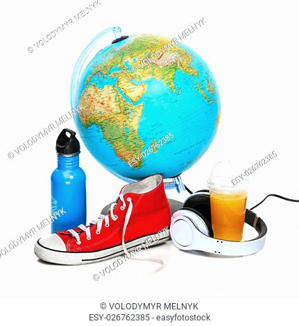 The blue globe, sneakers, thermos and headphones on white background. The travel, tourism and holidays concept