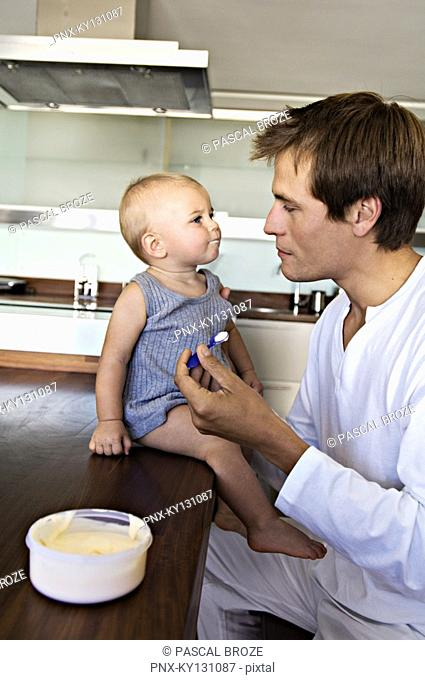 Father and son in kitchen, man feeding his baby, indoors