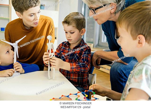 Children and pre-school teachers with wind turbine and anatomical model in kindergarten