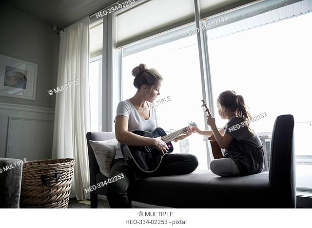 Daughter with ukulele watching mother playing guitar in living room
